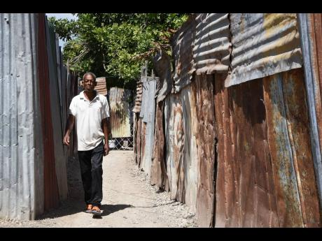 Delroy Young walks along a zinc-fenced pathway in Naggo Head, Portmore. Residents are hopeful that the blighted community can be transformed through significant real-estate investment.