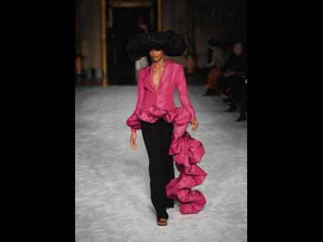 A model walks the runway at the Christian Siriano Fall-Winter 2021 at Gotham Hall during New York Fashion Week in a plunging, voluminous, fuchsia jacket.