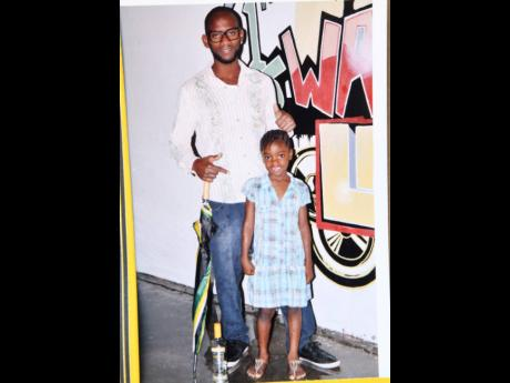 Navay Samuel poses with his daughter in this undated photo provided by his family. Samuel was among three people killed in Mongoose Town on Sunday.