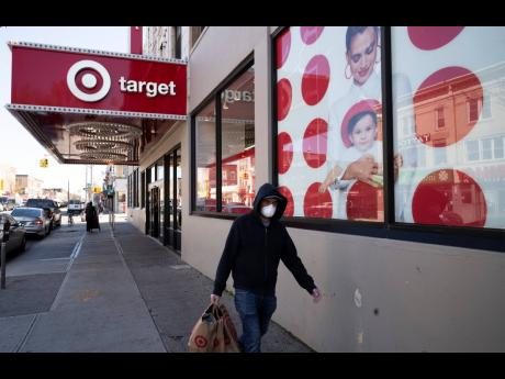 In this April 6, 2020 photo, a customer wearing a mask carries his purchases as he leaves a Target store, in the Brooklyn borough of New York.