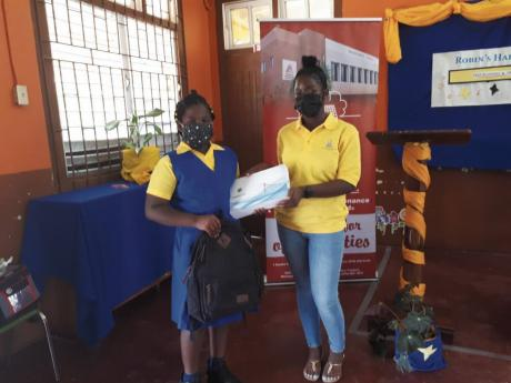Amelia Morgan (left), accepts her tablet and bag of school supplies from Christina Williamson, a past student of Robin's Hall Primary School on Friday, February 26.