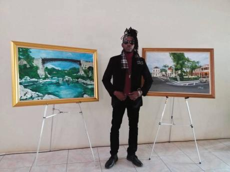 Artist Delroy Millwood with paintings of the Spanish Town Bridge (left) and Spanish Town Square.