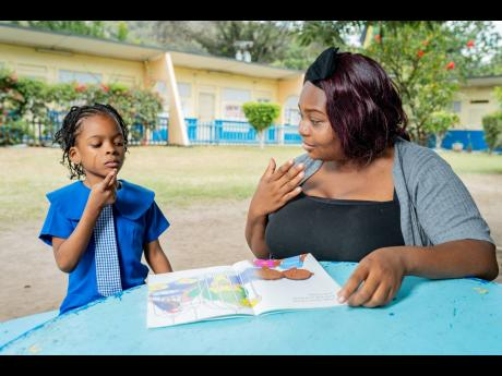 Diana Stewart (right), whose child attends Danny Williams School For The Deaf in St Andrew, communicates through sign language with Cataleya Sawyers, who is a student at the school.