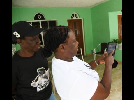 Vinnette Robb Oddman, sister of Bunny Wailer, looks at photos of the late musician on a cell phone at the family home in Nine Miles, St Ann, on Tuesday. Behind her is another sister, Monica Robb.