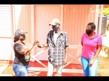 BOOM Brand Manager Keteisha McHugh hands over the keys to a newly built Food For The Poor (FFP) house for 74-year-old Bogle Waldeman in Zion Hill, St Mary, on February 23. Looking on is FFP Development and Marketing Manager Marsha Burrell-Rose. The retired