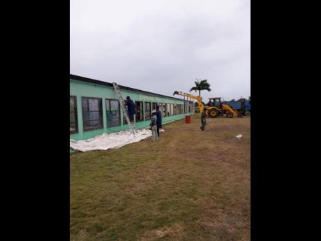 Workmen dismantle the old tote board, located on the infield at Caymanas Park ,recently. Supreme Ventures Racing and Entertainment Limited has committed to erect a new, modern display at the facility.