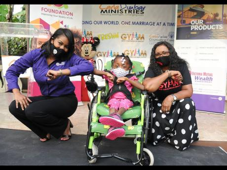Suzannie Chambers (left), assistant manager, treasury, Victoria Mutual (VM) Wealth Management Ltd, and Carla Dunbar (right) of the Carla Dunbar Ministries, share a photo opportunity with seven-year-old Dominique White, following the recent VM Foundation do