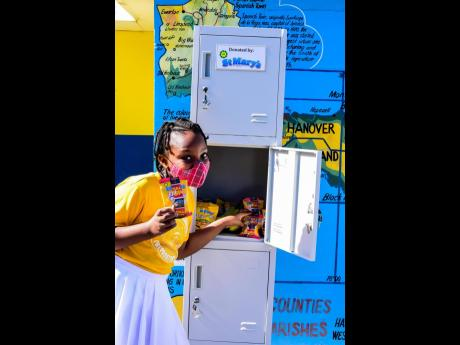 Portmore Missionary Preparatory grade five student Courtney Dawson grabs a JP St Mary's Extra Crunchy Banana Chips from the lockers donated by JP St Mary's. Three four-door lockers were handed over last month as part of the company's overall thrust t
