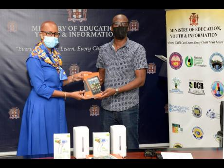Minister of Education, Youth and Information Fayval Williams (left) receives a tablet from director of the Building Alternative Bridges for Success Foundation, Adrian Reynolds. Occasion was a ceremony for the handover of $500,000 worth of supplies in suppo