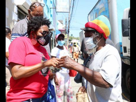 Montego Bay Chamber and Industry President Janet Silvera goes through a COVID-19 information pamphlet with a pedestrian along St James Street in Montego Bay yesterday.