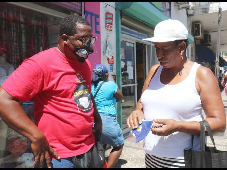 Dominic Shaw of the Montego Bay Chamber of Commerce and Industry discusses the importance of observing the protocols to reduce the risk of COVID-19 transmission with a woman after handing her a mask along St James Street during the #MaskMoBay campaign yest