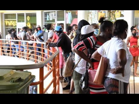 In this April, 2020 photo, long lines are seen in Pavilion Mall, Half-Way Tree, as people waited to collect their compassionate care grant paid out by the Government from a Western Union branch. A year on, Jamaica is grappling with increasing number of COV