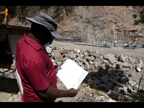 Project Manager Orville Clarke looks over the blueprint as work progresses on the rehabilitation of a breakaway along the Gordon Town main road in St Andrew. The road was damaged during heavy rains last November and is now impassable to vehicular traffic.