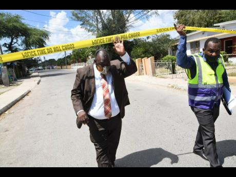Independent Commission of Investigations' Nigel Morgan (left), director of complaints, Eastern Region, and Clive Robinson, senior investigator, approach the murder scene where Kenrick Genas who was fatally shot in Sydenham Park, St Catherine, on Thursday
