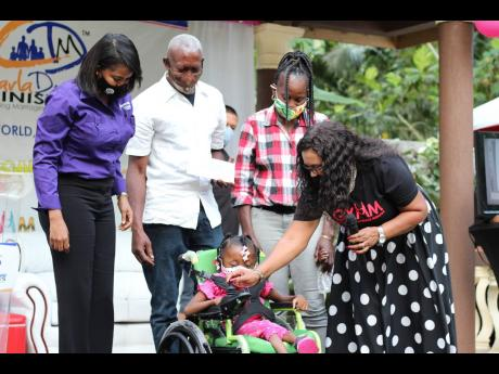 From left: VM Wealth's Suzannie Chambers, assistant manager for treasury, and Peter White and Jacqueline Rodney-White, parents of Dominique, look on as Reverend Dr Carla Dunbar instructs their daughter, who was diagnosed with osteogenesis imperfecta at b