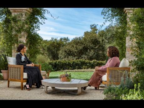 Meghan (left), The Duchess of Sussex, speaks with Oprah Winfrey.