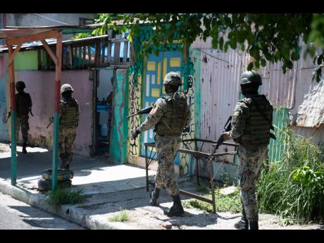 In this October 2020 photograph, members of the Jamaica Defence Force make their way along Fleet Street, in Parade Gardens. Jamaica recorded just over 1,300 murders last year, a vast majority were shooting deaths.