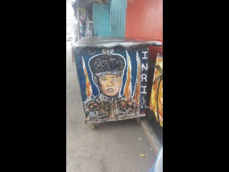 HRH enflamed painted on a roadside stall at Friendship Lane, Cross Roads.