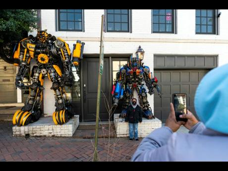 Ayden, 6, poses for a photograph in front of sculptures of Transformers Bumblebee ( left) and Optimus Prime, which flank the entrance of Georgetown University biochemistry professor Newton Howard's home.