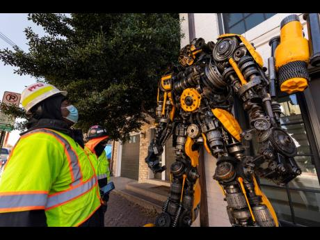 Workers stop to admire and photograph a sculpture of Transformers Bumblebee.