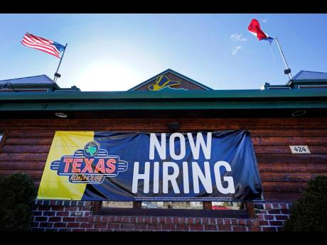 A restaurant displays a 'Now Hiring' sign, Thursday, March 4, 2021, in Methuen, Massachusetts.