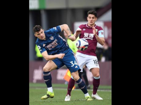 Arsenal's Granit Xhaka (left) and Burnley's Ashley Westwood challenge for the ball during the English Premier League match between Burnley and Arsenal at Turf Moor stadium in Burnley, England, yesterday.