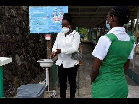 A student of The Morant Bay High School stands six feet in line from Marsha Ford-Bryan, acting principal, as she washed her hands on February 5, 2021.