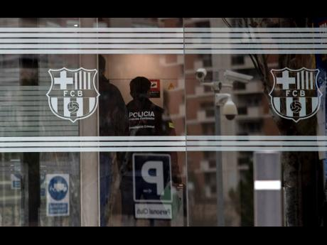 In this file photo dated Monday, March 1, 2021, Catalan police enter FC Barcelona's offices in Barcelona, Spain, where they detained several people in a search and seize operation.  More than 110,000 Barcelona club members will elect a new president tod
