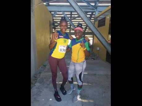 Rusea's High School sprinters Aalliyah Francis (left) and Lavanya Williams pose together at Stadium East after competing at the Jamaica Athletics Administrative Association Qualifying meet at the National Stadium yesterday.