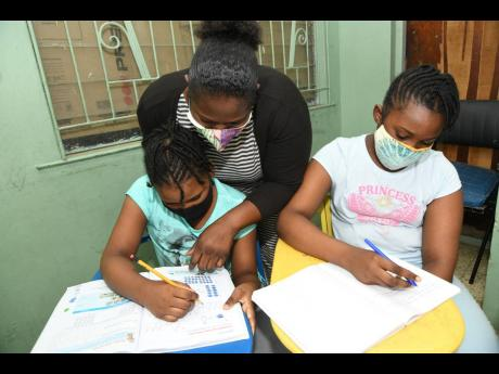 Toni-Ann McKenzie (centre) helps nieces Brihanna McKenzie (left) and Sapphire Farr at their home in Swallowfield, St Andrew, on Sunday. Despite her visual woes, Toni-Ann's love for children has spurred her to accommodate several kids from the neighbourho