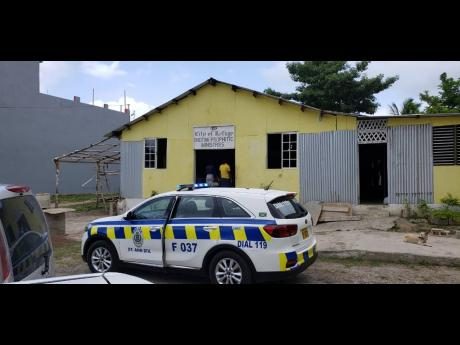 A police vehicle is parked in front of the City of Refuge Endtime Prophetic Ministries church in Windsor Heights, St Ann's Bay, last week.