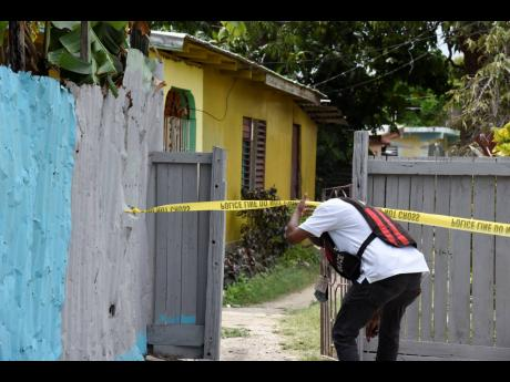 An investigator enters the yard where 24-year-old Cody McLaughlin was gunned down in Duncans Pen, St Catherine.