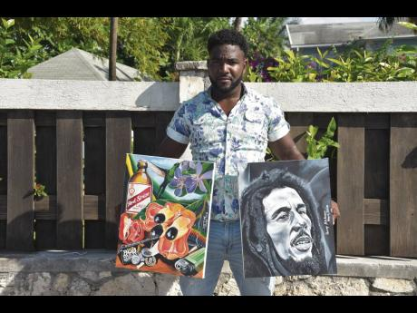 Roxroy Hutchinson holds two of his art pieces.