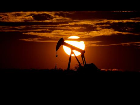 In this April 8, 2020 photo, the sun sets behind an idle pump jack near Karnes City, United Sates.