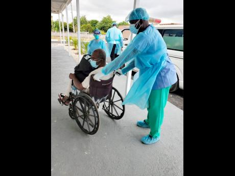 One of six patients being transferred to the newly constructed ward to treat COVID-19 patients at the Falmouth Hospital in Trelawny yesterday.