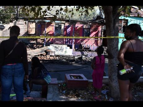 Residents observe a razed building on Beeston Street in Kingston on Monday. Latoya Whyte, 37, was found dead in the blaze.