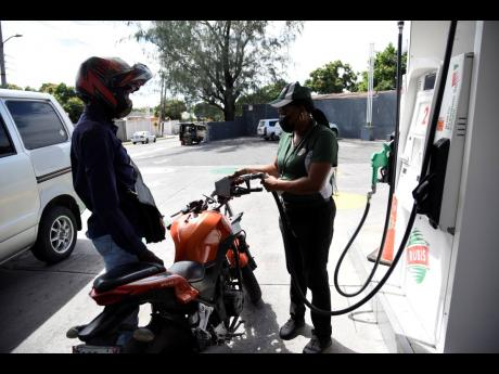A motorcyclist watches as an attendant pumps petrol at a RUBiS service station in Vineyard Town, Kingston.