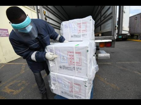 A staffer at the Marcus Garvey Drive warehouse removing the five boxes of AstraZeneca vaccine on Monday.