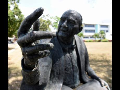 A building looms in the background of a statue of Philip Sherlock at The University of the West Indies, Mona. There are fresh safety concerns at the campus as coronavirus cases mount.