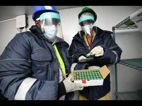 Norman Smith, National Health Fund warehouse operations supervisor, and Marcia Yetman, public health nurse and regional nursing supervisor, inspecting AstraZeneca vaccines inside a cold-storage facility on Marcus Garvey Drive, Kingston, on Monday.