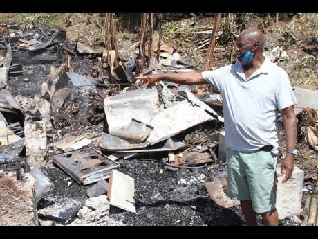 Easton Sharpe, 73 years old, of Commissary district, Frankfield, points to a burnt-out stove from his restaurant which he had been operating for 18 years.