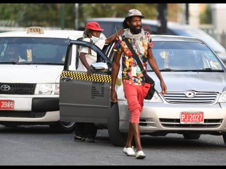 A taxicab operator awaits passengers at South Parade in downtown Kingston on Tuesday. Registered cabbies who paid licence fees in 2020 will have one-third of those costs underwritten by the Government in 2021.