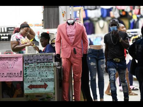 Employees at a clothing store located at West Parade, Kingston, engage in discussion as a customer walks out on Tuesday afternoon. Finance Minister Dr Nigel Clarke announced $3 billion in grants for those earning below the income tax threshold and who have