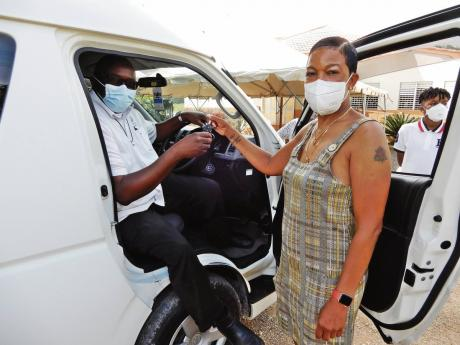 Maureen Russell of Motra Foundation hands the keys of the Toyota Hiace bus to Father Garvin Augustine of the Mustard Seed Communities.