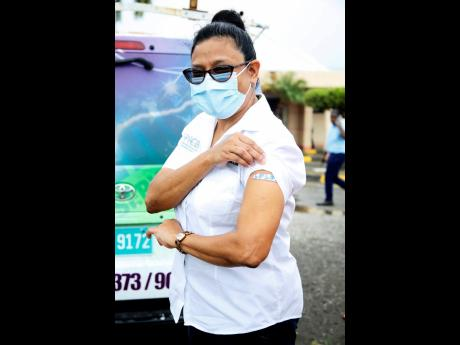 Dr Jacquiline Bisasor-McKenzie, chief medical officer, proudly displays her vaccination Band-Aid on Wednesday. She got the jab at the Spanish Town Hospital.