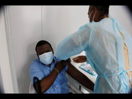 Chad Clarke, pharmacist at the May Pen Hospital, winces as he gets his first dose of the COVID-19 vaccine from a public health nurse on Wednesday.