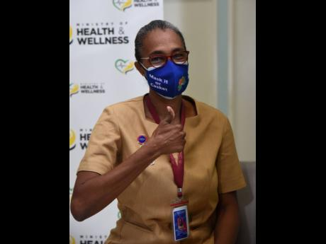 Marcia Thomas-Yetman, a public health nurse, gives the thumbs up after getting the COVID-19 vaccine on Wednesday.