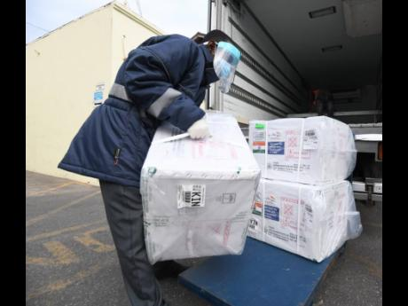 A staffer removes the five boxes of AstraZeneca vaccines, gifted to Jamaica by Government of India, at the National Health Fund's warehouse on Marcus Garvey Drive, Kingston, on Monday.
