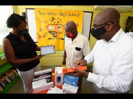 Haile Selassie High School Principal Lorenzo Ellis (centre) sorts through some of the tablets, face masks, soap dispensers and hand sanitisers donated to the institution yesterday with past students Georgina Henry-Smith and Milton Morrison yesterday. The d