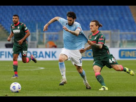 Lazio's Luis Alberto and Crotone's Jacopo Petricone (right) compete for the ball during a Serie A match between Lazio and Crotone at Rome's Olympic stadium, yesterday.